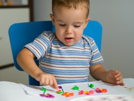 Petit gar�on et fleurs de p�te � modeler color�e
