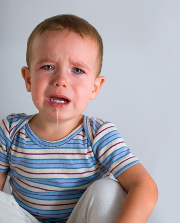 whimper: Cute crying boy on gray background
