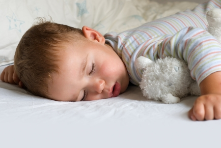 child sleeping: Dulce sue�o - ni�o durmiendo con oso blanco Foto de archivo