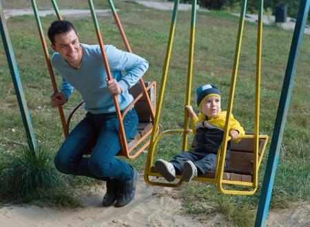Heureux p�re et fils mignon sur une balan�oire ancienne