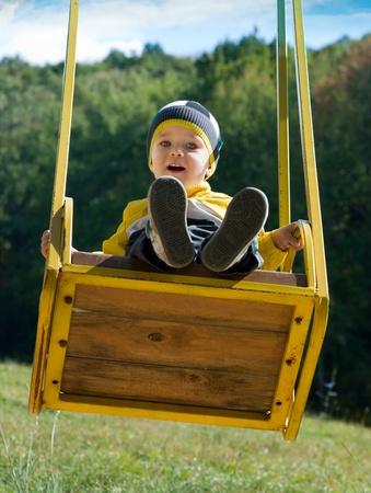 Mignon petit gar�on sur une balan�oire jaune