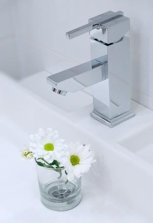 Gros plan du robinet salle de bain moderne avec des fleurs