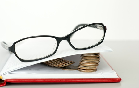 Glasses, book and piles of coins