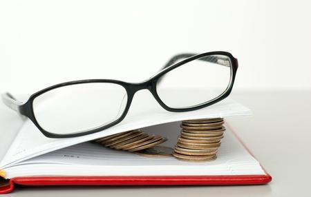 Lunettes, livre et des piles de pi�ces de monnaie
