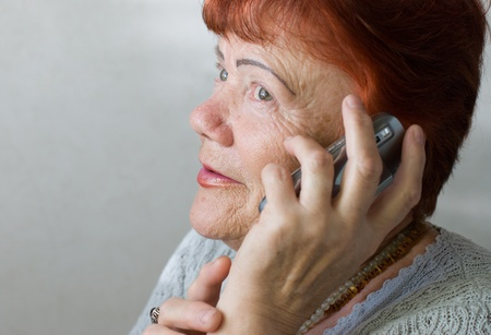 Portrait of seventy year old woman with cellphone photo