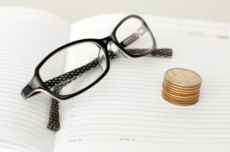 Business glasses, diary and piles of coins Stock Photo