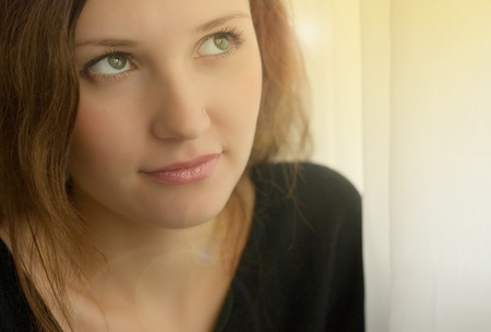 Portrait of beautiful young woman near the window photo