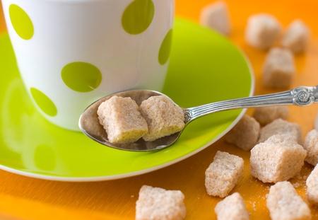 Coupe et cuill�re avec du sucre brun sur une plaque