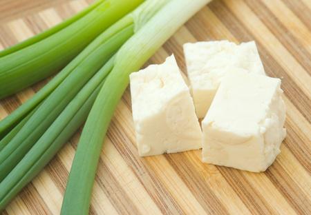 Le fromage en cubes avec de l'oignon vert sur un comptoir de cuisine Banque d'images