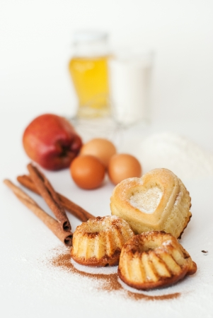 Heart-shaped cake and ingredients for baking