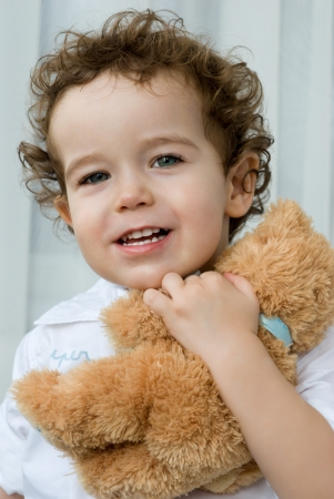 Curly-haired boy with a teddy bear Stock Photo