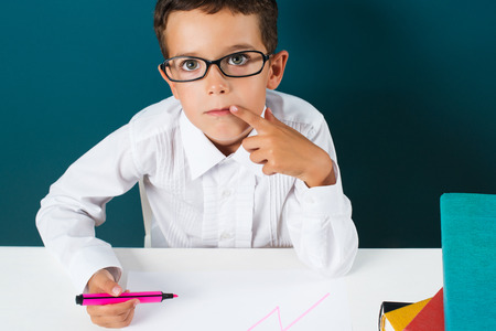 bewildered: Pensive cute boy with glasses sitting at a table