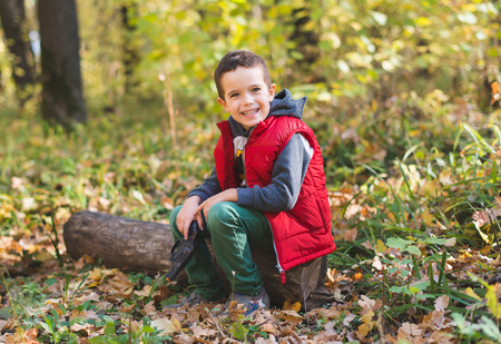 joyfull: Joyfull boy sitting on log in autumn forest