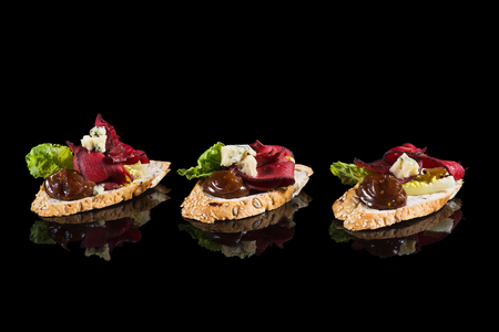 Bruschettas with beef and cheese on black background