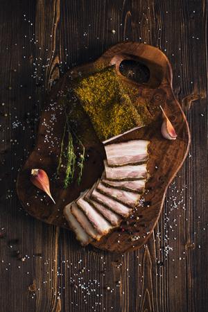Sliced smoked brisket with garlic, wooden background
