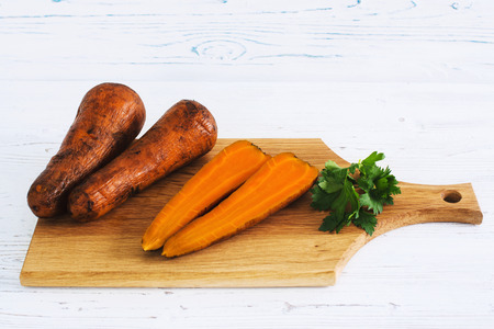 Boiled carrots and parsley on board, light wooden background Stock Photo