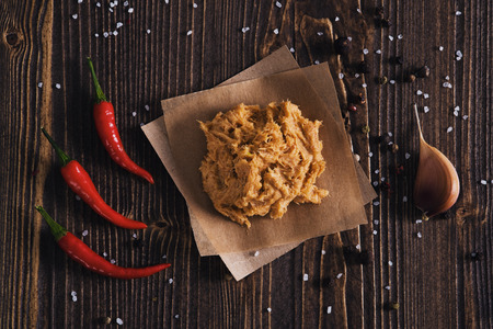 Lard with salt, chili pepper and garlic, wooden background
