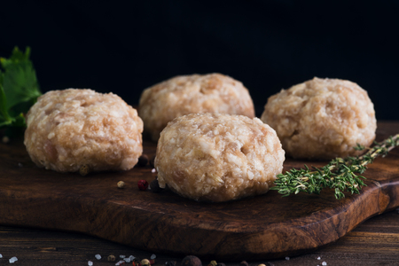 Uncooked meatballs in a dark rustic wooden setting Stock Photo