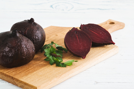 Boiled beets on board, light wooden background
