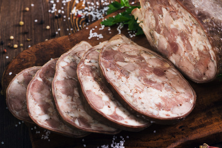 Sliced pork saltisons with herbs on a slate cutting board on wooden background Stock Photo