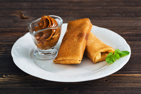 Pancakes with condensed milk on a plate, wooden background