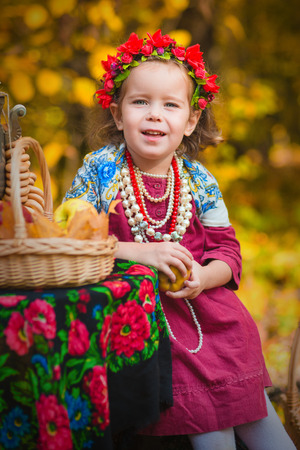 handkerchief: Adorable toddler girl wearing a colorful national ss on tea party in autumn forest Stock Photo