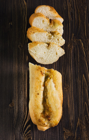 Top view of a sliced of baguette with herbs and spice, dark wooden background