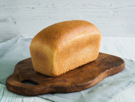 Loaf of bread on cutting board on wooden background
