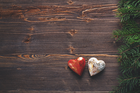 White and red hearts and fir branches, wooden background