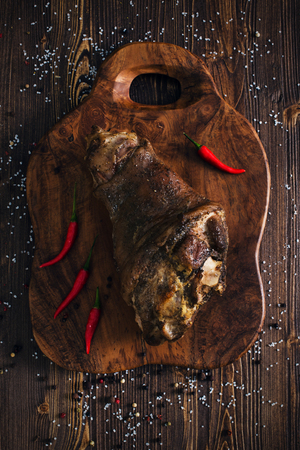Whole roasted pork knuckle with pepper, wooden background