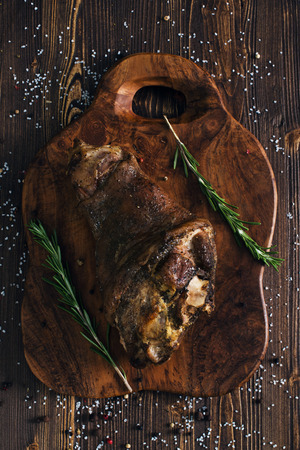 Whole roasted pork knuckle, wooden background