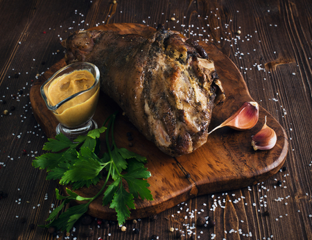 Whole roasted pork knuckle with mustard, wooden background