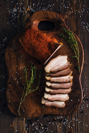 Sliced smoked brisket with spice, wooden background