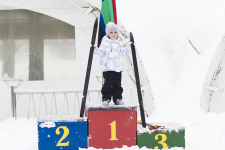 Little girl with skis on a pedestal