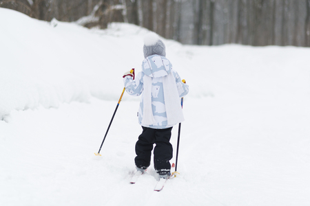 Child cross-country skiing in the forest