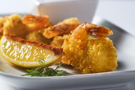 Crispy prawns with lemon slice on plate