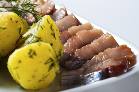 Herring fish slices with potatoes on the plate Standard-Bild