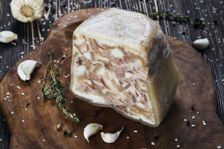 Headcheese on a slate cutting board on wooden background