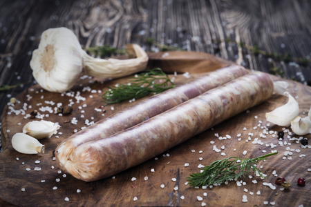 Raw sausages with garlic and parsley on the cutting board