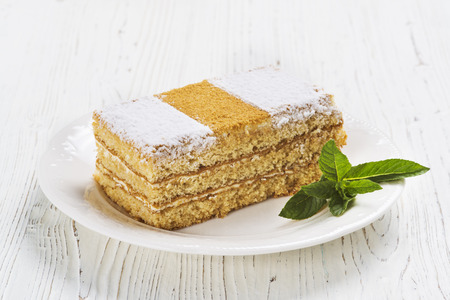 Honey cake on the plate on light background Standard-Bild