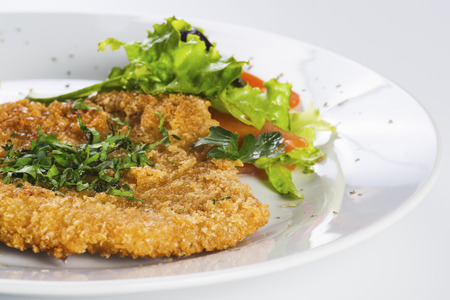 Crispy baked  pork chop served with salad on a plate Standard-Bild
