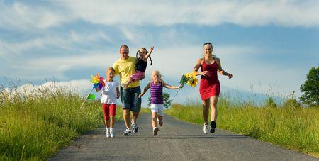 Familia con tres niños corriendo por una colina