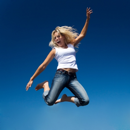 A young and beautiful woman jumping into a perfect blue sky photo