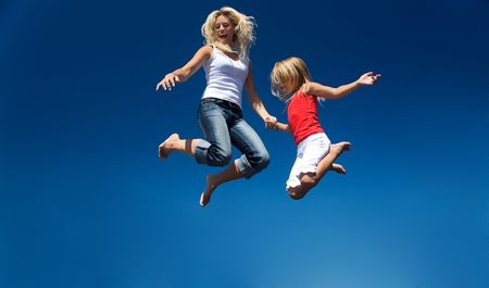A mother and her daughter jumping high having lots of fun photo