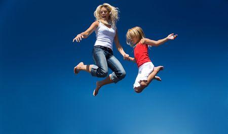 persona saltando: Una madre y su hija de saltar alto teniendo muchos de diversi�n
