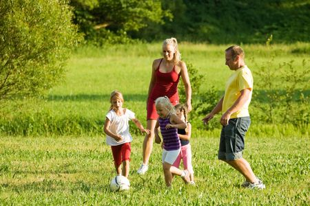 Happy family playing football (well, soccer for North America) on a green, sunlit meadow Stock Photo - 3307390