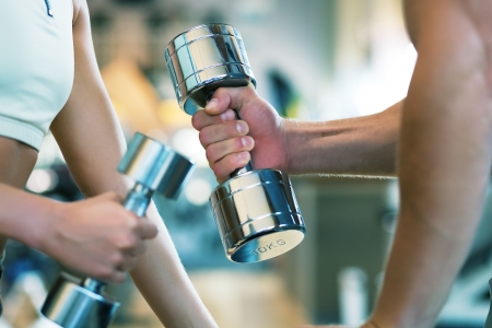 barbell: Two people (male  female) lifting dumbbells, shallow depth of field