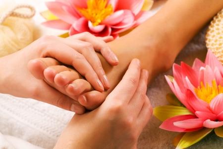 ногами: Woman enjoying a feet massage in a spa setting (close up on feet)
