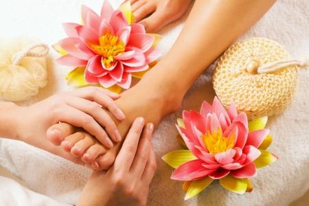 La mujer goza de un masaje de pies en el establecimiento de un spa (cerca de los pies)