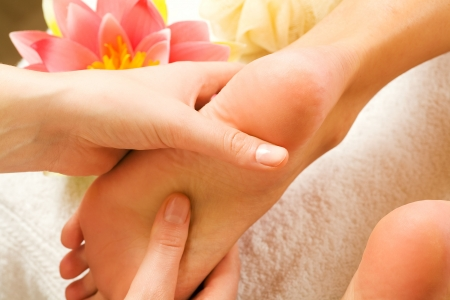 reflexology: Woman enjoying a feet massage in a spa setting (close up on feet)
